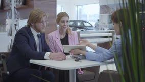 De jonge gelukkige familie sluit een overeenkomst over de aankoop van een nieuw voertuig De autohandelaar in een modieus kostuum  stock footage