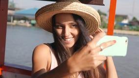 De jonge Gelukkige Gemengde Vrouw die van de Rastoerist op Houten Thaise Boot drijven en Selfie-Foto nemen die Mobiele Telefoon m stock videobeelden