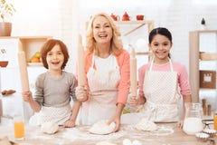 De jonge gelukkige grootmoeder samen met kleine gelukkige kleinkinderen kneedt deeg voor koekjes in keuken stock foto