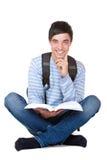 De jonge gelukkige knappe mannelijke student leest studieboek Royalty-vrije Stock Foto