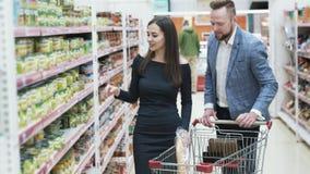 De jonge gelukkige man en de vrouw kiezen producten in winkel stock videobeelden