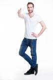 De jonge gelukkige mens met duimen ondertekent omhoog in toevallig. Stock Foto's