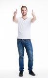 De jonge gelukkige mens met duimen ondertekent omhoog in toevallig. Stock Afbeeldingen