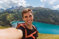 De jonge gelukkige mens neemt een selfie op de bovenkant van de berg in de Zwitserse alpen stock foto's