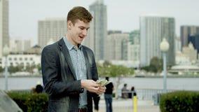 De jonge gelukkige mens telt zijn geld op een stoep stock video