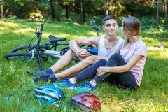 De jonge gelukkige mensen zijn in liefde Het lopen in het park op fietsen Stock Foto's
