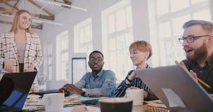 De jonge gelukkige millennial onderneemster die op multi-etnisch modern kantoor spreken assoieert en vergadering, team die slaan  stock video