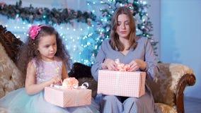 De jonge Gelukkige Moeder met haar Weinig Zoete Dochter opent Giften, kijkt Binnenkomend en verheugt zich op de Achtergrond van stock footage