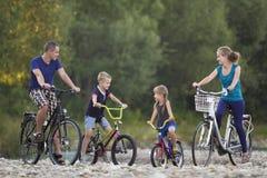De jonge gelukkige moeder, de vader en twee leuke blonde kinderen, jongens en meisjes berijdende fietsen pebbled rivierbank op va stock foto