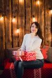 De jonge gelukkige mooie die vrouw met giftdozen zit dichtbij muur voor Kerstmis in de ruimte van het huis wordt verfraaid Vrolij Royalty-vrije Stock Foto's