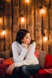 De jonge gelukkige mooie die vrouw met giftdozen zit dichtbij muur voor Kerstmis in de ruimte van het huis wordt verfraaid Vrolij Royalty-vrije Stock Foto
