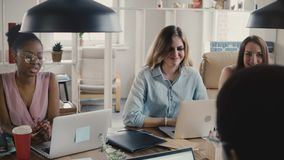 De jonge gelukkige mooie multi-etnische vrouwelijke collega's bespreken zaken door bureaulijst in modieuze zolder die ruimte4k co stock video