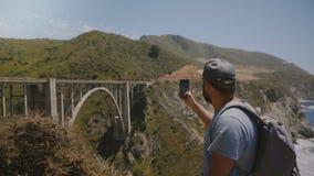 De jonge gelukkige opgewekte toeristenmens met rugzak neemt smartphonefoto van iconische Bixby-Kreekbrug in Big Sur Californië stock videobeelden