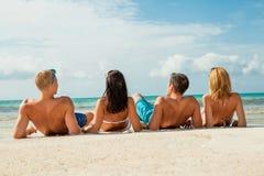 De jonge gelukkige pret van vriendenhavin op het strand stock foto
