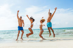 De jonge gelukkige pret van vriendenhavin op het strand stock afbeelding
