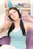 De jonge gelukkige student met hoofdtelefoons luistert muziek Royalty-vrije Stock Afbeeldingen