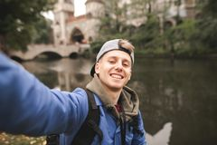 De jonge gelukkige toerist maakt een sephi op de achtergrond van het meer en het kasteel en glimlacht stock foto