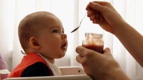 De jonge gelukkige vader voedt zijn het fruitpuree van de zoonsbaby stock videobeelden
