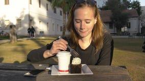 De jonge gelukkige vrouw eet cake openlucht in het park stock videobeelden