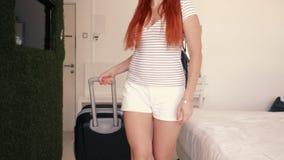 De jonge gelukkige vrouw gaat met een koffer in haar hotelruimte binnen stock video