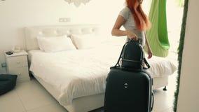 De jonge gelukkige vrouw gaat met een koffer in haar hotelruimte binnen stock videobeelden