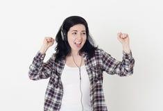 De jonge gelukkige vrouw in grote hoofdtelefoons zingt zijn favoriete lied en dans tegen een witte muur Royalty-vrije Stock Fotografie