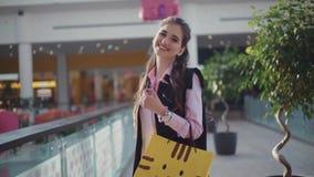 De jonge gelukkige vrouw in het roze overhemd loopt in het winkelcentrum Het aantrekkelijke meisje omcirkelt cheerfully, het drag stock videobeelden