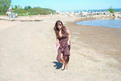De jonge gelukkige vrouw met glazen loopt langs het strand stock foto's