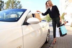 De jonge gelukkige vrouw met het winkelen doet in openlucht dichtbij de auto in zakken royalty-vrije stock fotografie