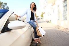 De jonge gelukkige vrouw met het winkelen doet in openlucht dichtbij de auto in zakken stock fotografie