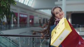 De jonge gelukkige vrouw met mooie samenstelling in het roze overhemd en het zwarte sleeveless jasje loopt in het winkelcentrum stock footage