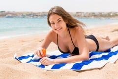 De jonge gelukkige vrouw rust op de handdoek dichtbij het overzees en beschermt haar huid op de hand met zonnescherm tegen de nev stock foto's