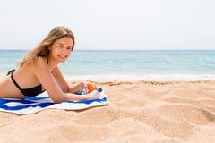 De jonge gelukkige vrouw rust op de handdoek dichtbij het overzees en beschermt haar huid op de hand met zonnescherm tegen de nev royalty-vrije stock foto