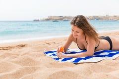De jonge gelukkige vrouw rust op de handdoek dichtbij het overzees en beschermt haar huid op de hand met zonnescherm tegen de nev royalty-vrije stock fotografie