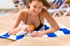 De jonge gelukkige vrouw rust op de handdoek dichtbij het overzees en beschermt haar huid op de hand met zonnescherm tegen de nev stock afbeelding