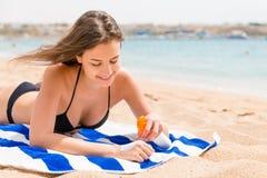 De jonge gelukkige vrouw rust op de handdoek dichtbij het overzees en beschermt haar huid op de hand met zonnescherm tegen de nev royalty-vrije stock afbeeldingen