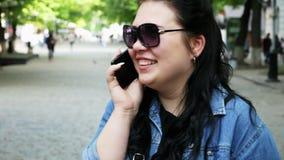 De jonge gelukkige vrouw spreekt emotioneel op de telefoon, lachend op de straat stock footage