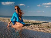 De jonge gelukkige vrouw in zonnebril, blauwe tunika zit bij de kust, lach en bekijkt het overzees zonnige dag Mooie Glimlachende royalty-vrije stock foto's