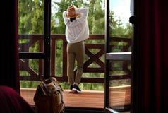 De jonge gelukkige vrouwenreiziger blijft in een hotelruimte royalty-vrije stock foto's