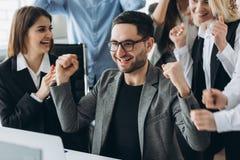 De jonge gelukkige zakenman met werkelijk indrukwekkende verwezenlijkingen, overwinningsdans, snelgroeiend beloond bedrijf, won e stock foto's