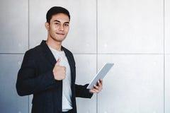 De jonge Gelukkige Zakenman Smiling en toont Duimen terwijl het Gebruiken van Digitale Tablet Status door de Industriële Concrete royalty-vrije stock foto