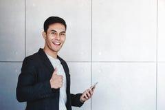 De jonge Gelukkige Zakenman Smiling en toont Duimen terwijl het Gebruiken van Smartphone stock afbeeldingen