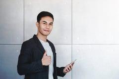 De jonge Gelukkige Zakenman Smiling en toont Duimen terwijl het Gebruiken van Smartphone royalty-vrije stock foto's