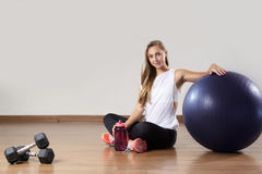 De jonge geschikte vrouw ontspant na opleiding dichtbij gymnastiek- bal Royalty-vrije Stock Foto