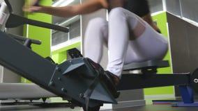 De jonge geschiktheidsvrouw maakt oefening op het roeien machine in gymnastiek Vrouwelijke atleet opleiding bij uitoefenaar in ge stock videobeelden