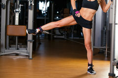 De jonge geschiktheidsvrouw voert oefening op heup met oefening-machine Kabeloversteekplaats in uit gymnastiek stock afbeelding