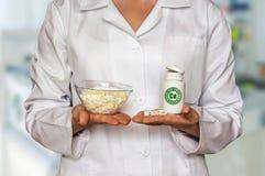 De jonge gestremde melk van de artsenholding en fles van pillen met vitaminen en Royalty-vrije Stock Fotografie