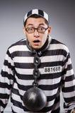 De jonge gevangene in kettingen tegen grijs stock afbeelding