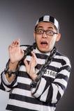 De jonge gevangene in kettingen tegen grijs royalty-vrije stock afbeelding