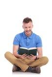 De jonge gezette mens leest zijn boek Stock Foto